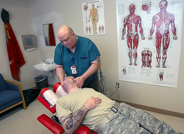 An Army report recommended the use of alternatives to pain drugs, including chiropractic care, massage and acupuncture. Here, Dr. Frank Lawler gives Spc. David Ash chiropractic treatment, January 7, 2011, in Tacoma, Washington. (Mark Harrison/Seattle Times/MCT)